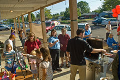 Chris Nordyke serves up hot dogs to a crowd at his State Farm agency's July barbe