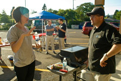 Rebecca Badger and Ryan Gardner from Visual People wait for the hot dogs to grill at Chris Nordyke State Farm's July barbeque